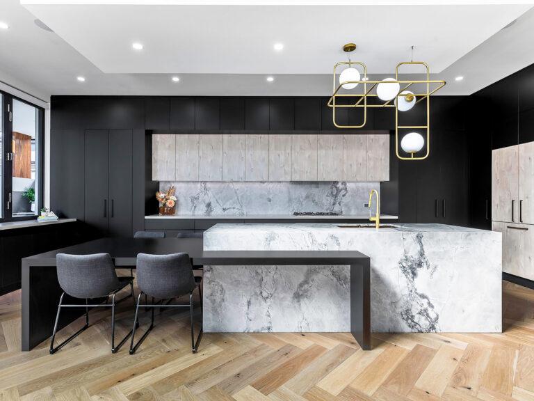 """This beautiful kitchen has doors and panels in Black Ultramatt and Angora Oak Woodmatt. The breakfast bar benchtop in Black Matt."""